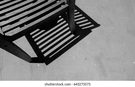 Part Wooden Garden Chair on patio tiles- showing sharp shadows Close up.Monochrome.