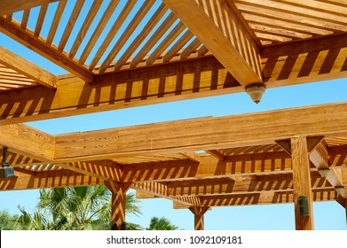 Part of the wooden roof structure on the gazebo on blue sky background.
