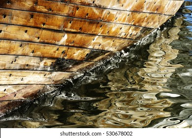 part of wooden ship sheathing, reflected in water