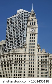 Part of the Wrigley Building clock in downtown Chicago, Illinois against a clear blue sky.