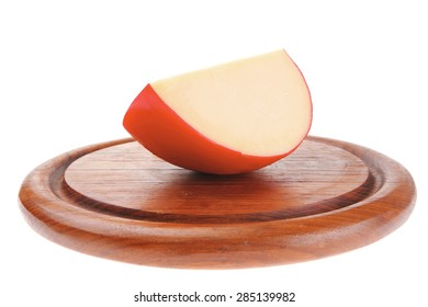 part of yellow cheese on dark wooden plate
