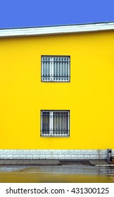 Part of yellow colored building wall with two windows closed metal grills vertical photo over blue cloudless sky