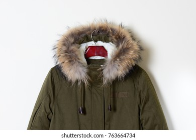 Part of the youth jacket with a hood with natural fur. Stylish winter outerwear on a hanger. Close-up.