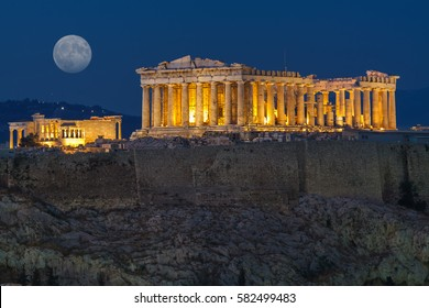 The Parthenon in Acropolis Hill in Athens, Greece shot in blue hour with the moon rising above the sky