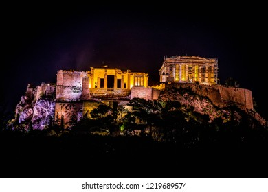 The Parthenon in Athens Greece lit up at night with lights.