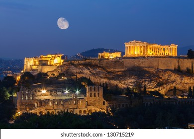 Parthenon and Herodium construction in Acropolis Hill in Athens, Greece shot in blue hour with moon in the sky