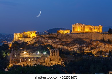 Parthenon and Herodium construction in Acropolis Hill in Athens, Greece shot in blue hour with the moon rising above the sky