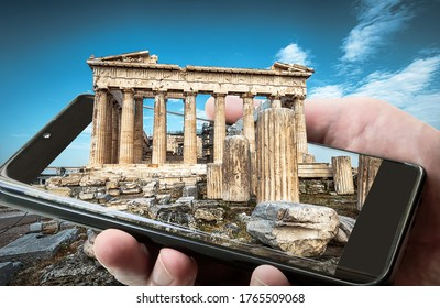 Parthenon on Acropolis of Athens, Greece. Picture of Athens landmark on smartphone screen, amazing photography of Ancient Greek monument and mobile or cell phone. Concept of travel and technology.