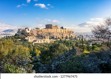 The pArthenon Temple of the Acropolis of Athens, Greece, over the old town Plaka covered in light snow during winter time