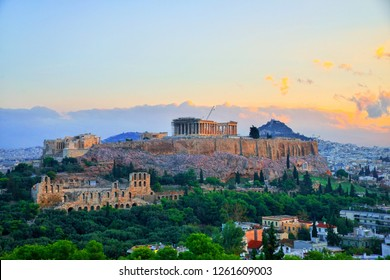 Parthenon temple in Acropolis Hill in Athens, Greece shot in blue hour over the old town during colorful sunset with pink and purple clouds in the sky
