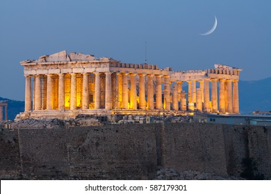 Parthenon temple in Acropolis Hill in Athens, Greece shot in blue hour with the moon rising above the sky