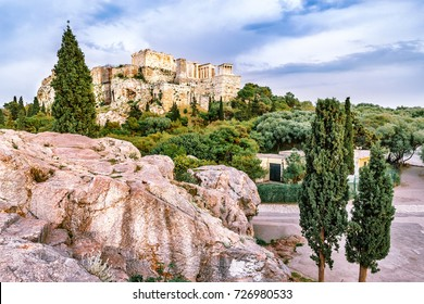 The Parthenon, view from Philosophic stone over cypress trees. Modern days, Restored ancient Greek ruins, extremely famous and popular travel destination in Athens, Greece, Europe.
