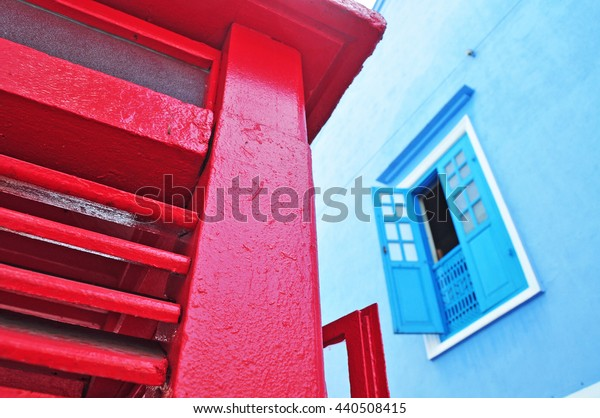 partial close up view of a red wooden booth. blue wooden window in the background.