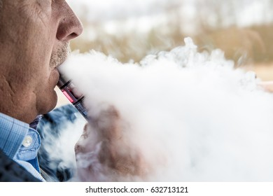 Partial face from side view of a old man smoking electronic cigarette