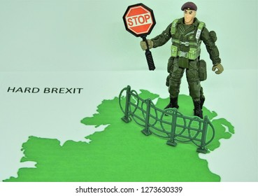 Partial map of Ireland with a toy soldier standing on the Northern Ireland section of the map holding a 'Stop' sign behind a fence border. The words 'Hard Brexit' are to the left of the map