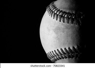 Partial shot of a baseball in black and white against a black background