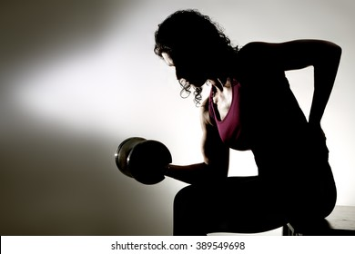 Partial silhouette of a fitness trainer doing seated bicep curls.  White background with deep shadows.