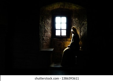 Partial silhouette of a woman in medieval dress sitting in the dark looking out of a bright window in the depths of an ancient castle