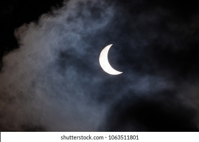 Partial solar eclipse viewed through clouds