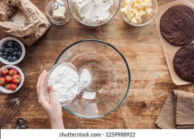 partial top view of woman holding flour and preparing dough for delicious homemade cake