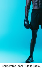 partial view of african american boxer in shorts and senakers on blue background