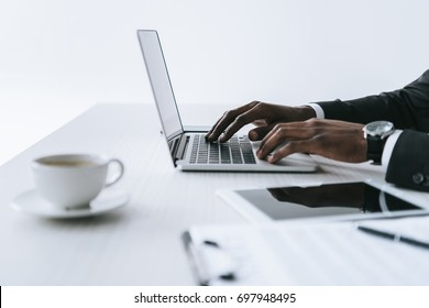 partial view of african american businessman typing on laptop at workplace isolated on white