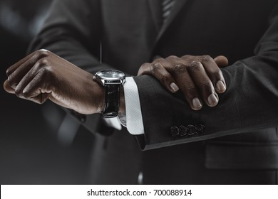 partial view of african american businessman checking time on watch