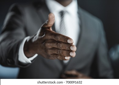 partial view of african american businessman with outstretched hand