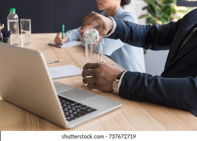 partial view of african american businessman pouring water into glass at workplace with laptop