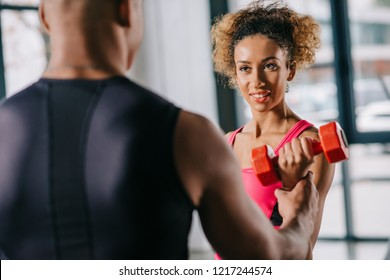 partial view of african american male trainer helping sportswoman to exercising with dumbbell at gym