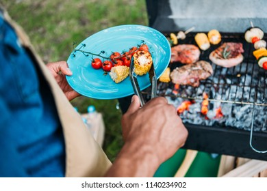 partial view of african american man wit tongs putting grilled vegetables on plate during bbq in park