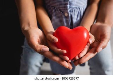 partial view of african american mother and daughter holding red heart model in cupped hands together