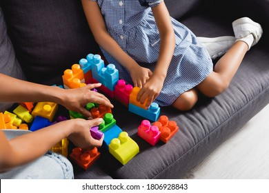 partial view of african american nanny and child playing with multicolored building blocks on sofa