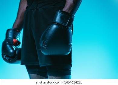 partial view of african american sportsman in shorts and boxing gloves on blue background