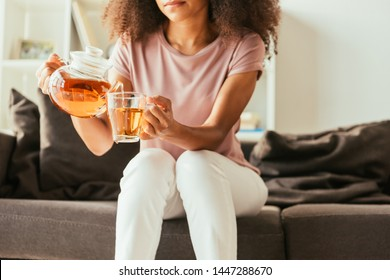 partial view of african american woman sitting on sofa and pouring tea into cup