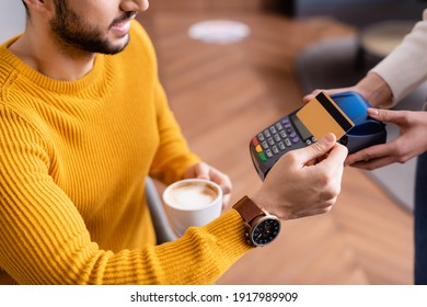 partial view of arabian man paying through payment terminal in hands of waitress
