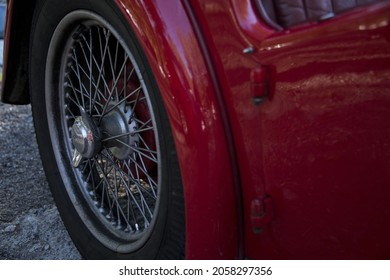 Partial view of the back fender of a red vintage car with spoke wheel