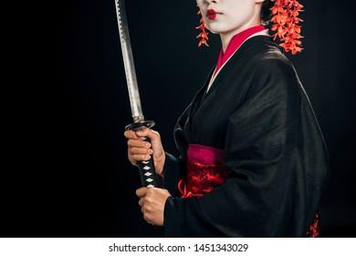 partial view of beautiful geisha in black kimono holding katana isolated on black