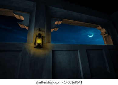 A partial view of a beautiful moon through a window of an old, traditional Arabic house with kerosene lantern hanging on the wall. Eid crescent moon with Islamic old architecture background.