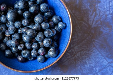 Partial view of blue bowl of blueberries on a blue coloured surface