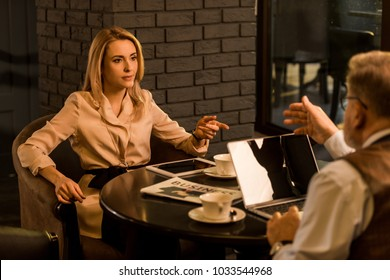 partial view of business people having meeting in cafe