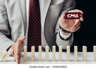 partial view of businessman holding brick with 'cmo' word and preventing wooden blocks from falling
