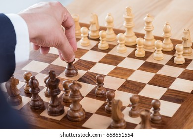 partial view of businessman holding chess figure while playing chess alone