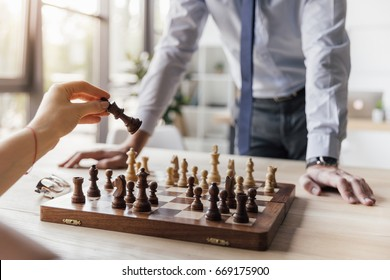 partial view of businessman playing chess with colleague in office