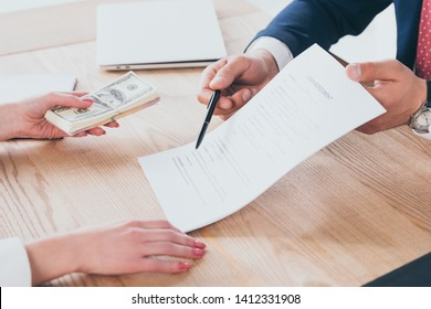 partial view of businessman pointing at signature place in loan agreement near woman holding dollar banknotes