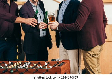 partial view of businessmen clinking drinks at table soccer in cafe