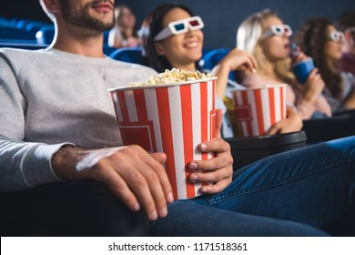 partial view of cheerful multiethnic friends watching movie together in cinema
