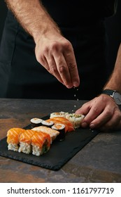 partial view of chef pouring sesame seeds on arranged sushi set on slate plate on dark tabletop