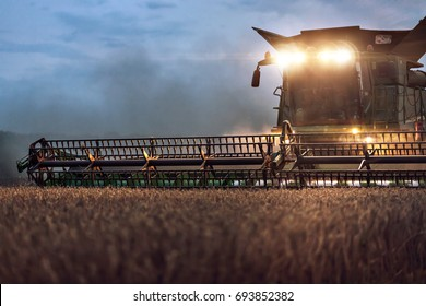 Partial view of a combine on a field at night