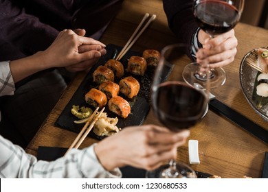 Partial view of couple holding hands while drinking wine and eating sushi in restaurant